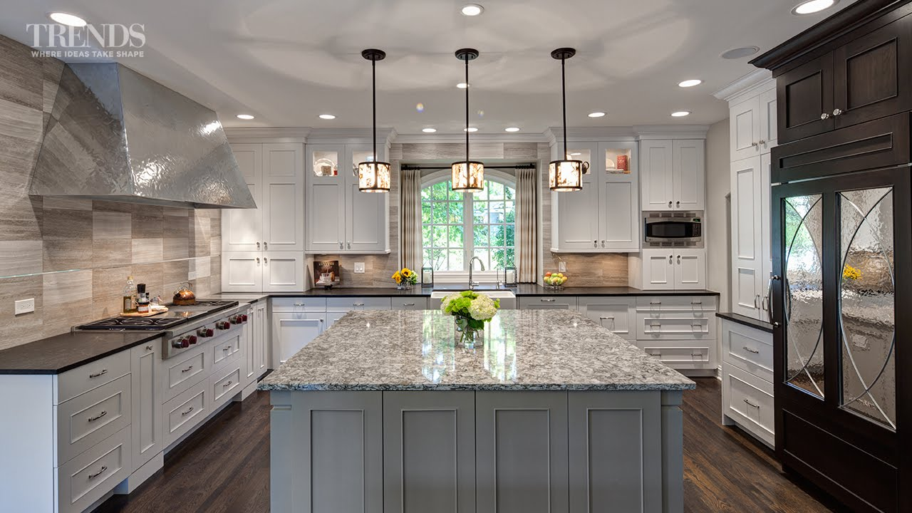 Large transitional kitchen design has two islands and a mix of white, taupe and dark colors.